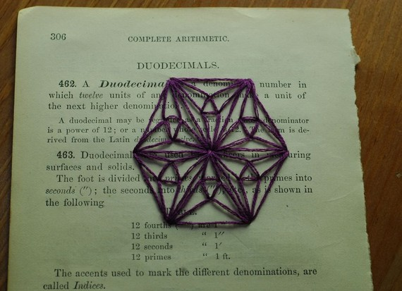 purple embroidered hexagon on antique book page