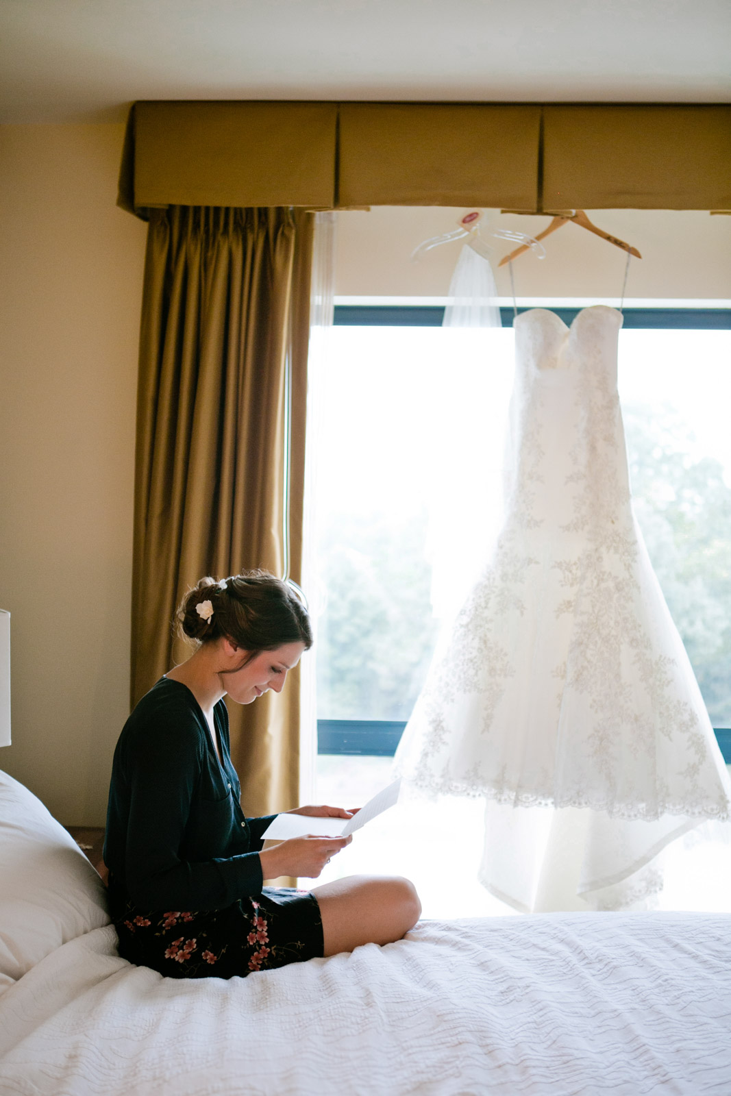 a bride sits and read her love letter from her groom with her wedding dress gracing the window behind her