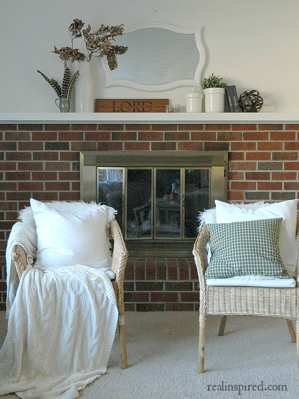 Sweet and Simple Fall Mantel: green plaid, wood tones, leaves, books, and turkey feathers.