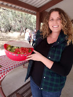 A woman with wavy brown hair wearing a black shirt and a green plaid vest holding a red plastic bowl full of salad.