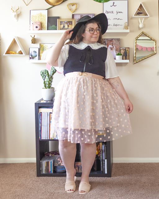 An outfit consisting of a black wide brim floppy hat, a white frilly collar over a white blouse with flouncy short sleeves, under a black mock neck dress tucked under a pink midi skirt with rosettes and pink slide sandals.