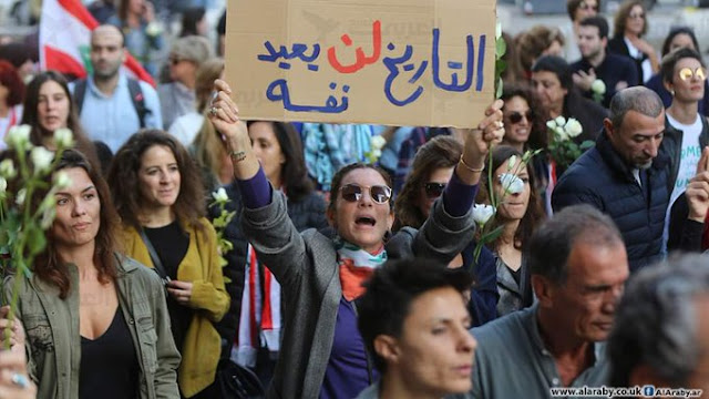 """History won't repeat itself"" a banner held by a Lebanese mom in a Beirut rally Hussein Baydoun for Al-Araby website"