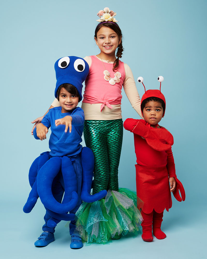 three kids in octopus, mermaid, and crab halloween costumes