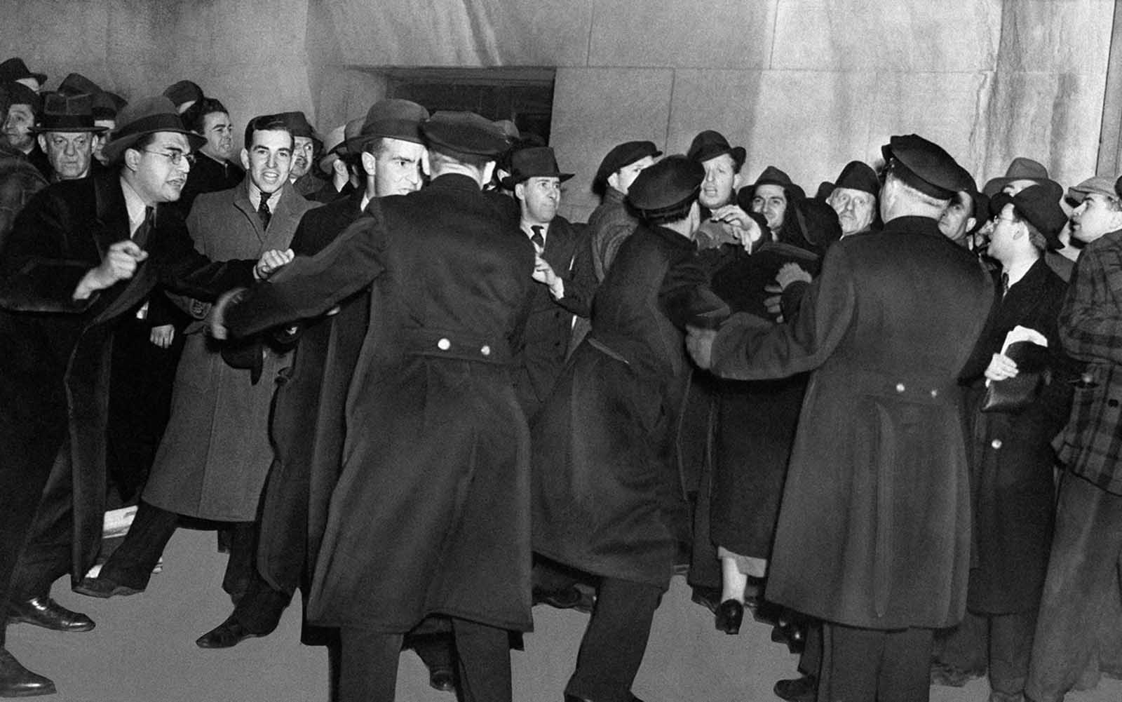 Original Caption: There's plenty of pushing and shoving as police try to keep streets clear in the immediate vicinity of Madison Square Garden in New York, on February 20, 1939 during a German-American Bund rally which had aroused a storm of protest from anti-Bund forces. There were strict police orders against picketing, and the 1,500 cops on duty in the area were instructed to halt all persons entering the neighborhood with provocative signs.