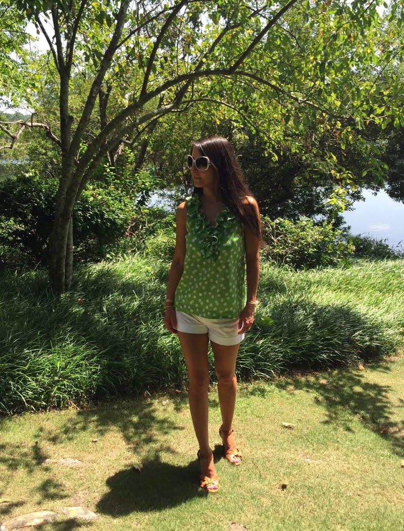 Dressed in white shorts with a green sleeveless ruffeled top and white sunglasses. Photo shot in front of trees by a lake.