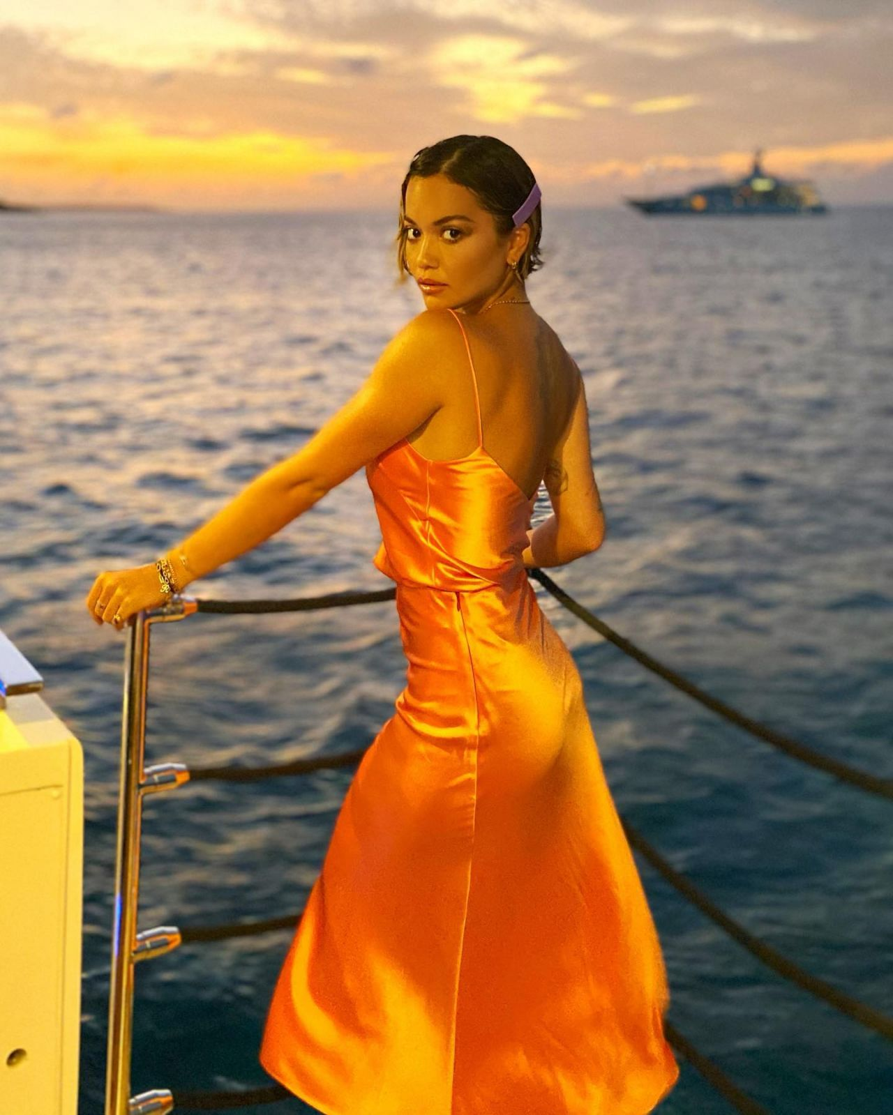 Rita Ora goes braless in slinky orange satin gown as she heads on scenic Christmas Day boat trip in St Barts