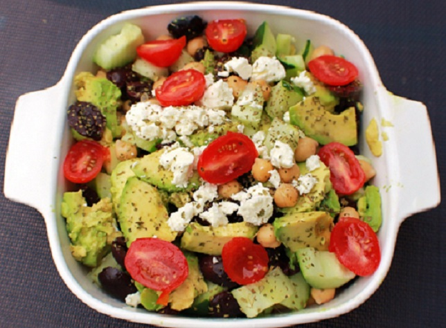 this is a healthy avocado greek salad with feta, olives avocado, tomato and chickpeas