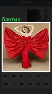 на девушке одето красное платье в виде большого банта