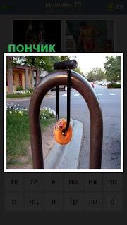 на улице на ограждении висит обычный пончик на шнурке