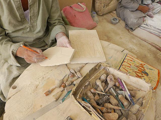 Mann zeichnet mit Bleistift traditionelles ägyptisches Motiv auf eine Steinplatte