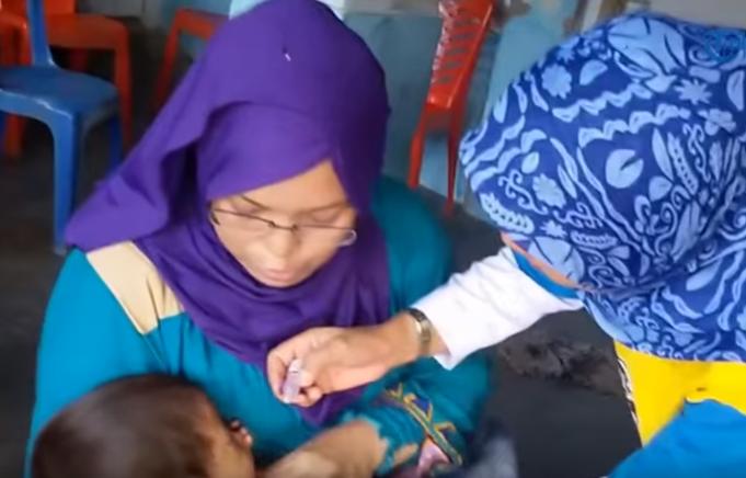 photo ibu gendong anak berikan vaksinasi polio