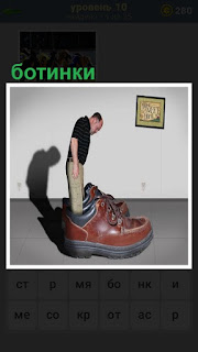 мужчина стоит в больших ботинках, которые выше его роста