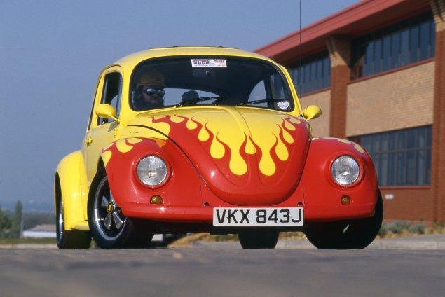 Vocho amarillo y rojo con llamas estilizada.