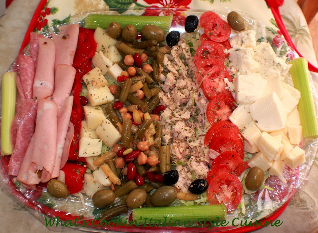 this is a large tray filled with fruits, nuts, meats, vegetables drizzled with Italian homemade dressing for Christmas day appetizer