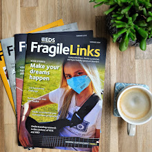 Birds eye view of a pile of magazines with the tile Fragile Links, next to the magazines is a cup of coffee and in the top right corner of the photograph is a green plant
