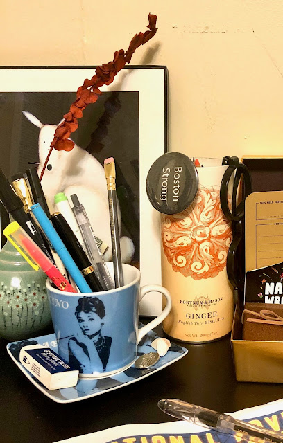 A view of my desk, focused on a blue Audrey Hepburn cup filled with pens and pencils