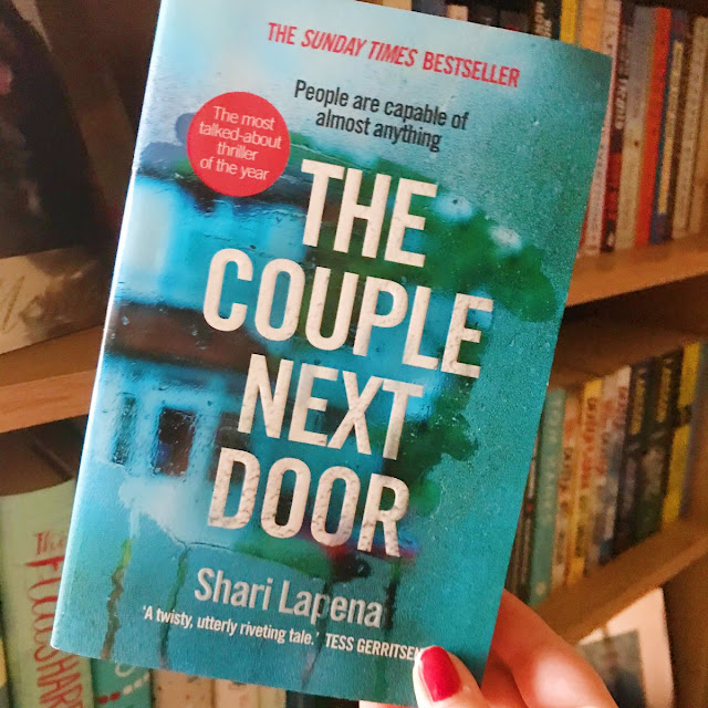 The couple next door by shari lapena held up in front of bookshelf