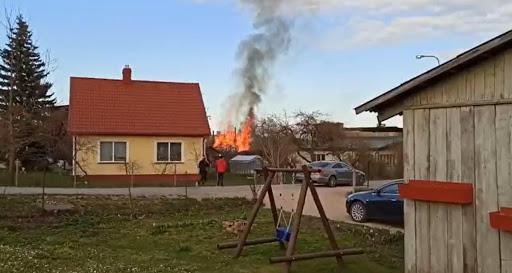 Aculiecinieki vēro liesmas, kuras ceļas no degošas palīēkas