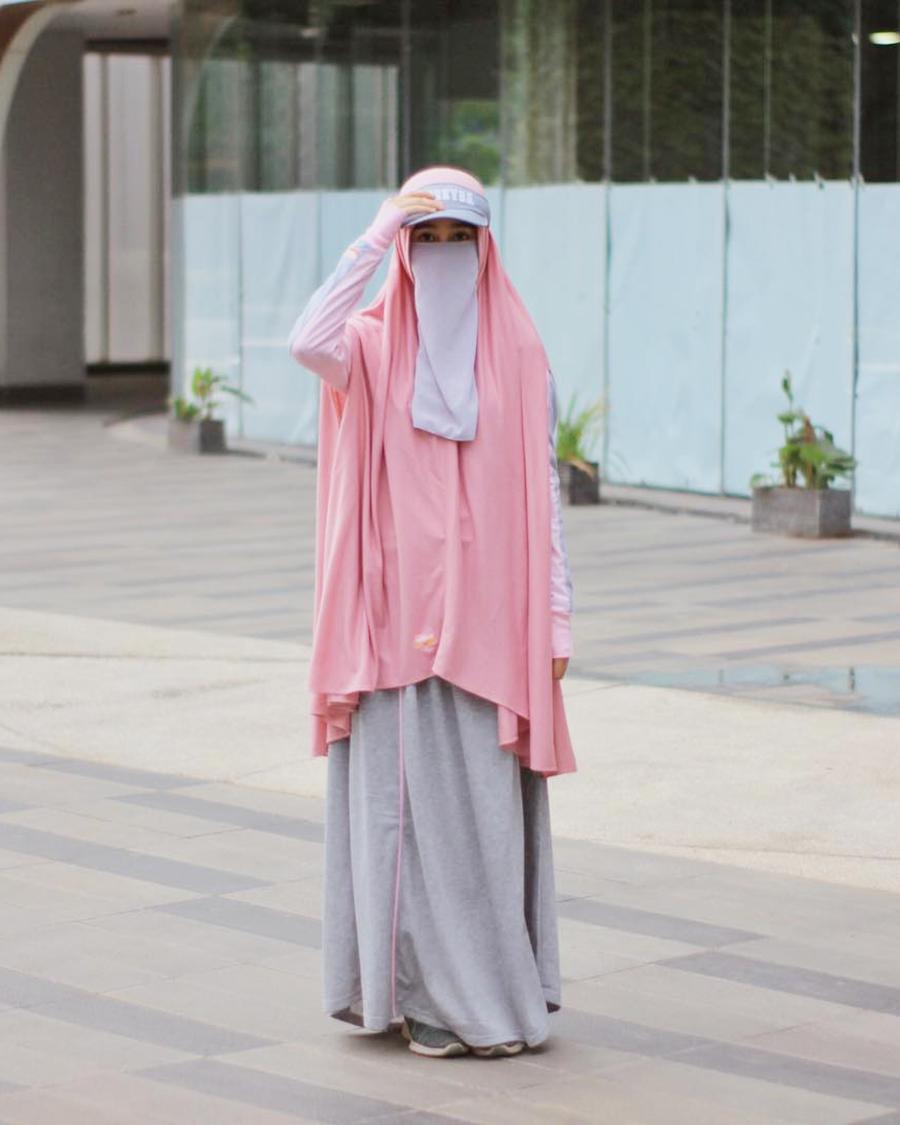 Cadar dan gamis pink pakai topi abu-abu