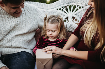 Child opening Gift for her Christmas gift during mini session