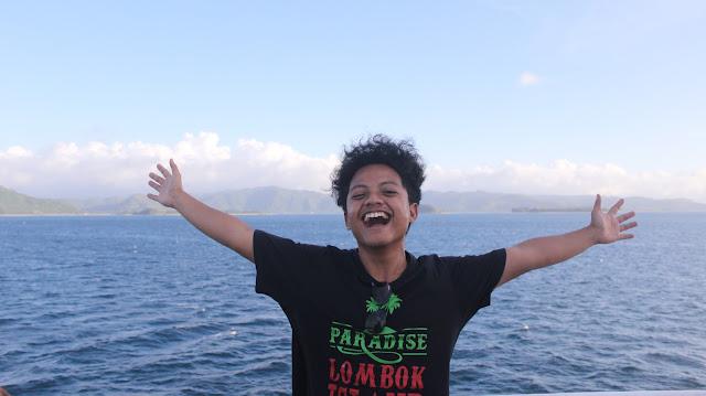 Saya sedang berdiri di atas kapal sendiri, dengan tangan terbuka dan tersenyum bebas di selat lombok