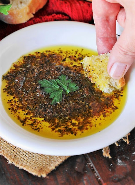 Dipping Bread into Simple Olive Oil Bread Dip Image