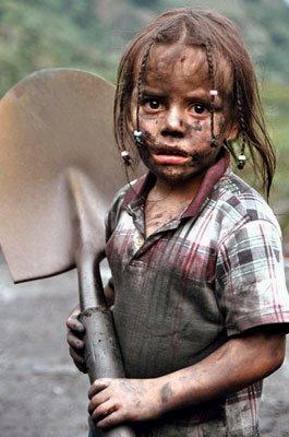 Foto de niña con el rostro sucio agarrando su lampa