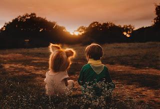 children watching sun emerging from the dark