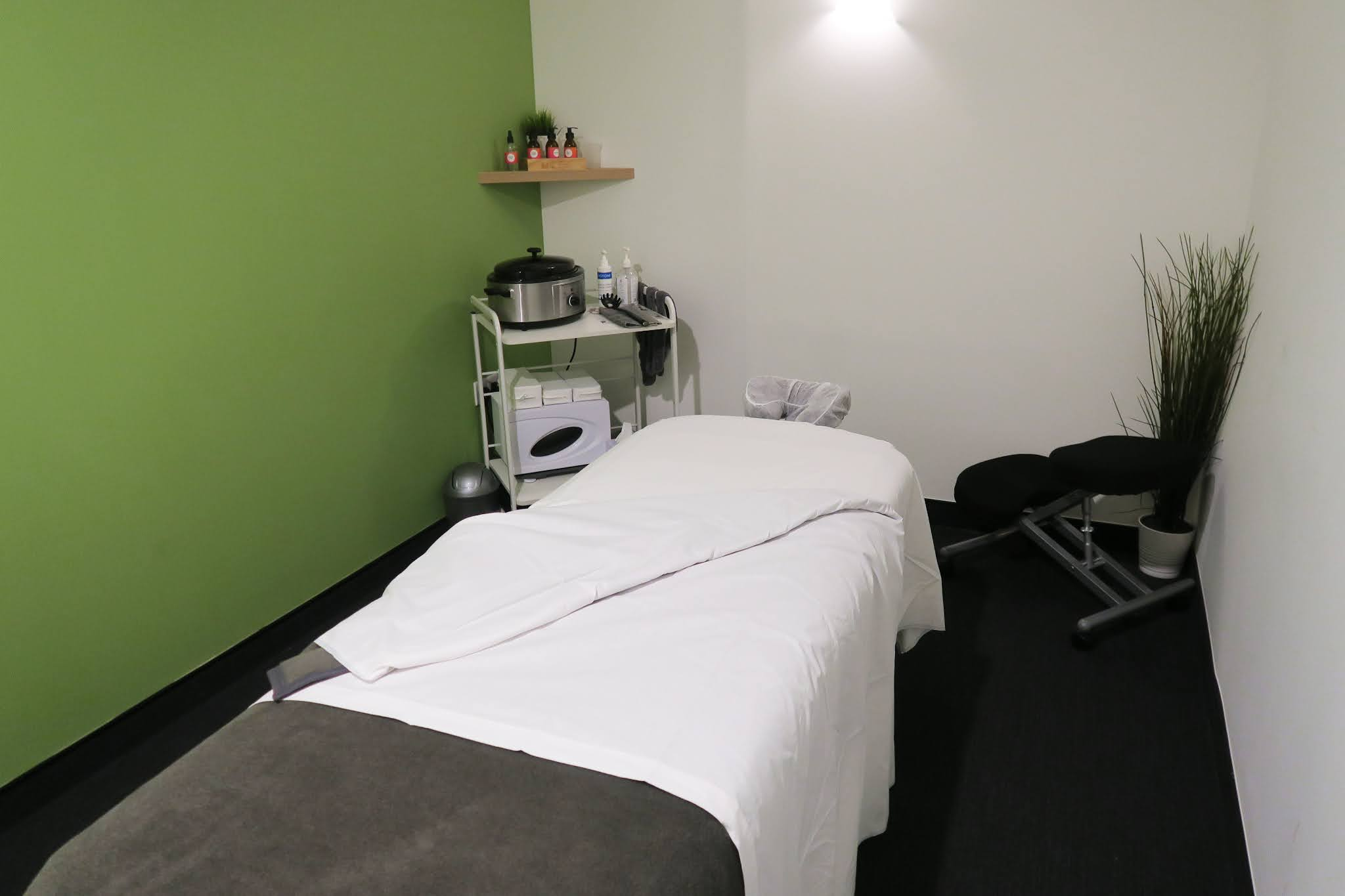Inside the treatment room. In the foreground the massage table can be seen and in the background is a table with a range of prodcts.