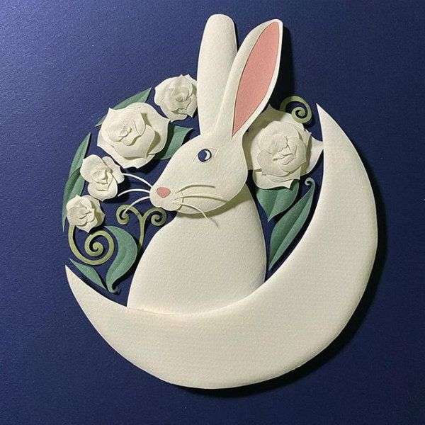paper sculpture rabbit in crescent moon surrounded by paper flowers