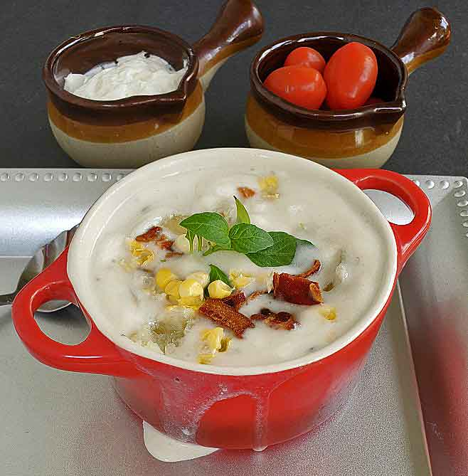 easy corn chowder made with cream corn and fresh corn in a red crock with sour cream and grape tomatoes in small crocks