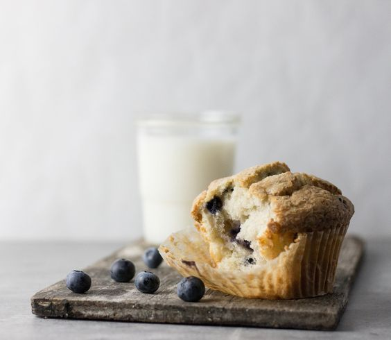 Blueberry muffin on wood board and glass of milk by Joan and Co.