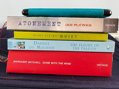 Books piled up on suitcase ready to take on holiday