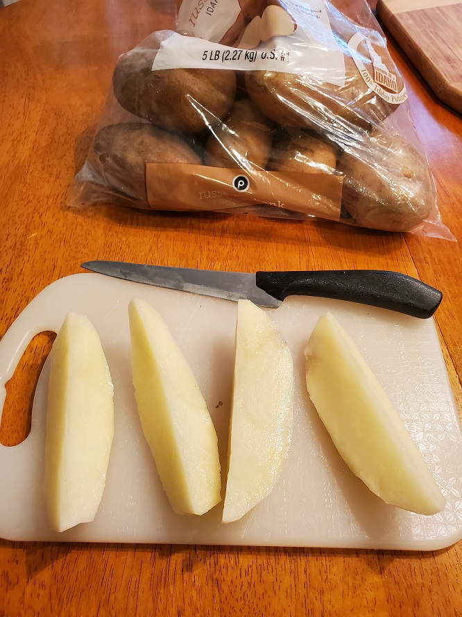 these are raw russet potatoes being cut with a paring knife into wedges for making baked parmesan crusted wedges topped with bread crumbs and cheese