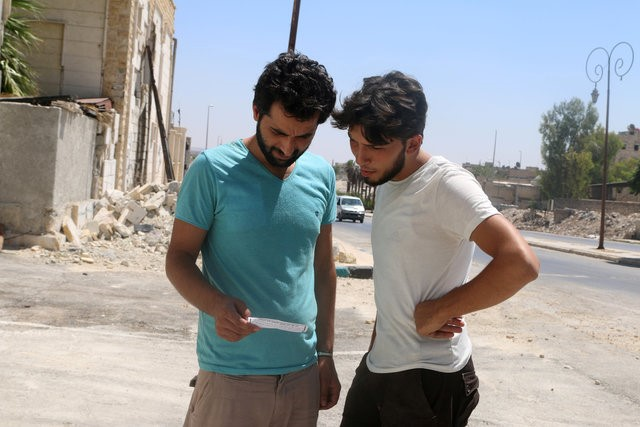 Men read one of the leaflets dropped by the Syrian army over opposition-held Aleppo districts asking residents to cooperate with the military and calling on fighters to surrender,