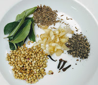 Coriander seeds,cumin, cloves, curry leaves, garlic for chicken ghee roast recipe