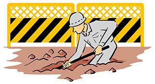 工事現場で作業員がスコップで穴を掘っている
