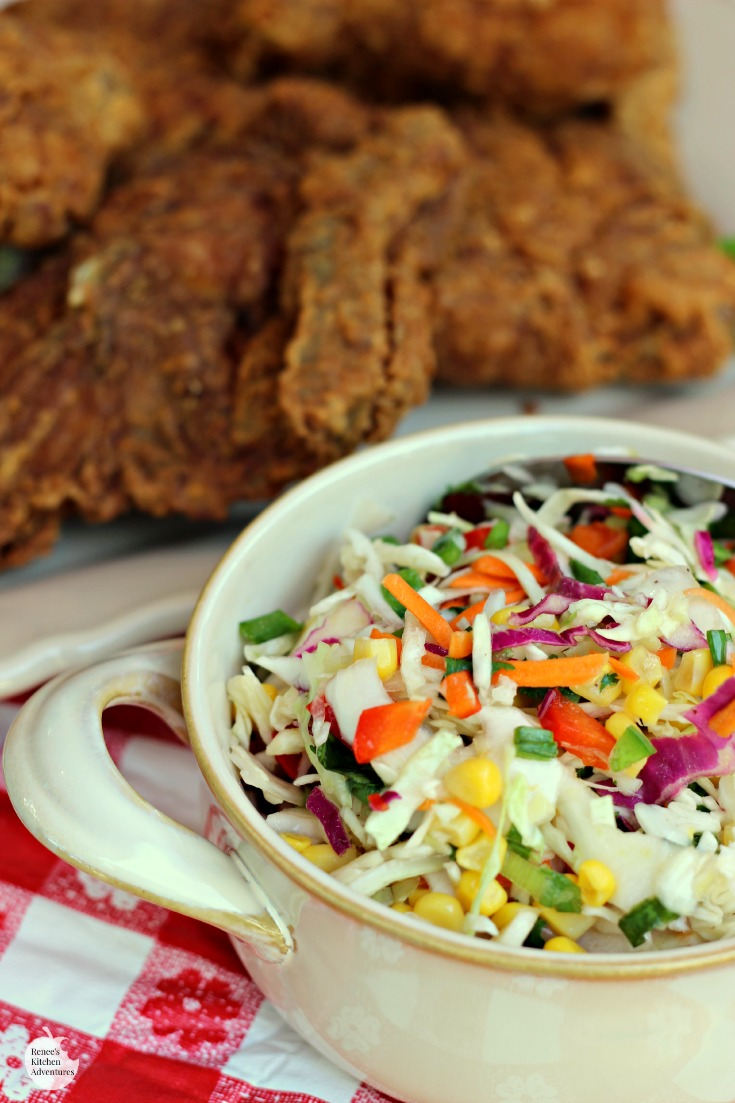 Firecracker Coleslaw by Renee's Kitchen Adventures close up in a bowl with fried chicken on a white platter in background