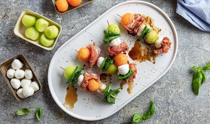 Espetos de melão, mussarela, tomate e presunto com manjericão
