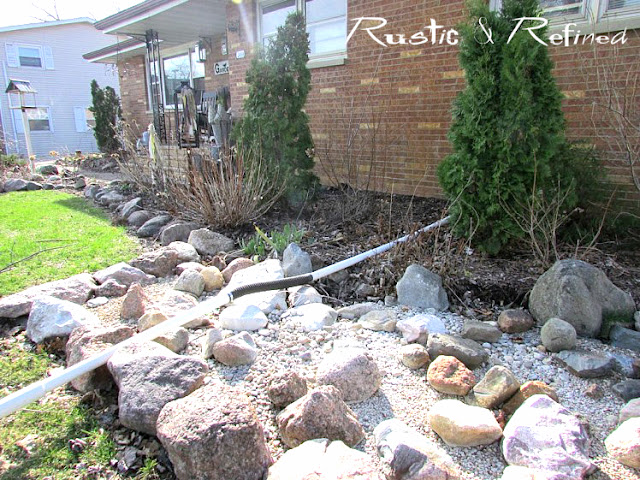 Before picture of a garden bed before the installation of a longer river creek bed