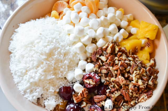 Ambrosia Fruit Salad Recipe in a bowl with fresh pineapple, mandarin oranges, cherries, coconut, pecans from Serena Bakes Simply From Scratch.