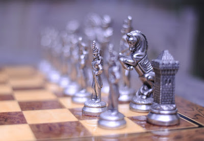 Chessmen on a chessboard with only a pawn and a knight in focus