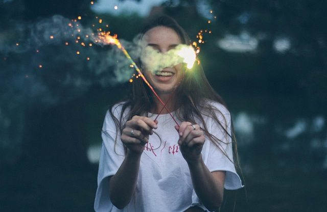 woman with fireworks smiling