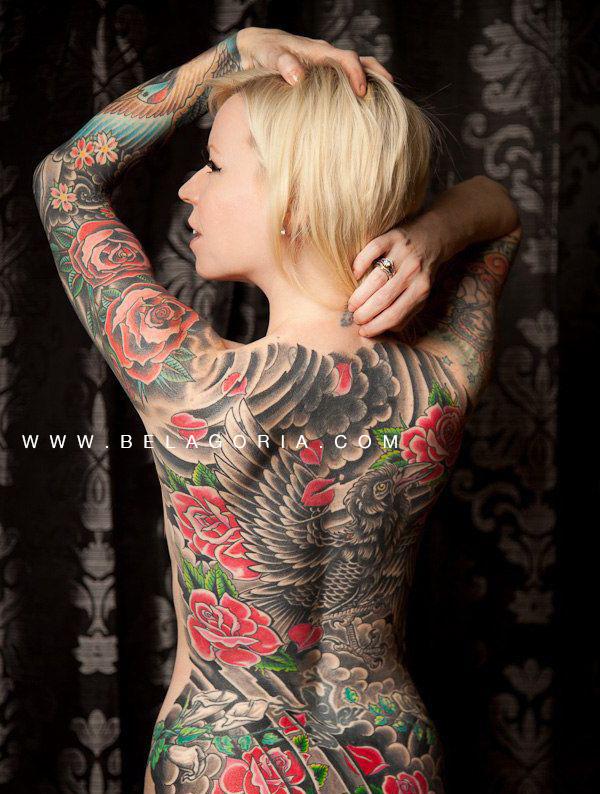 vemos a una mujer de espaldas, es rubia y lleva un tatuaje japones que le cubre toda la espalda