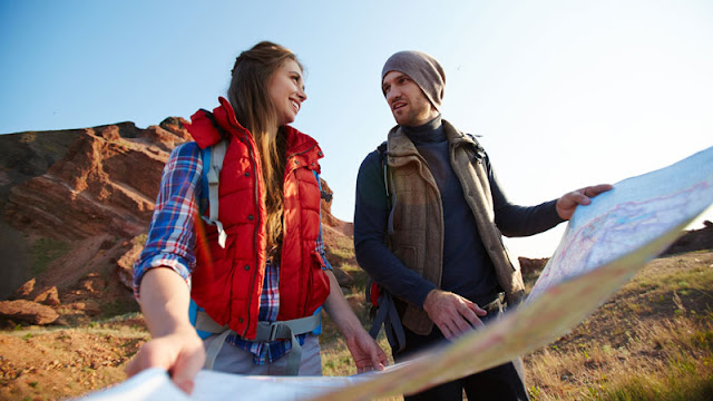 hiking couple examining map together