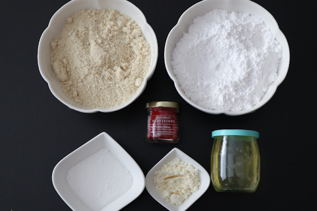 Ingredients for macaron baking in white bowls.