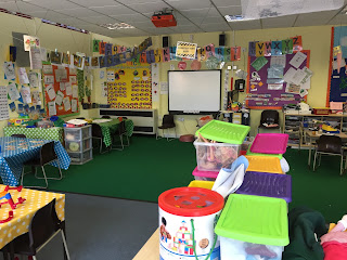 a reception school room with boxes of activities, tables and lots of things on the walls like alphabet and numbers