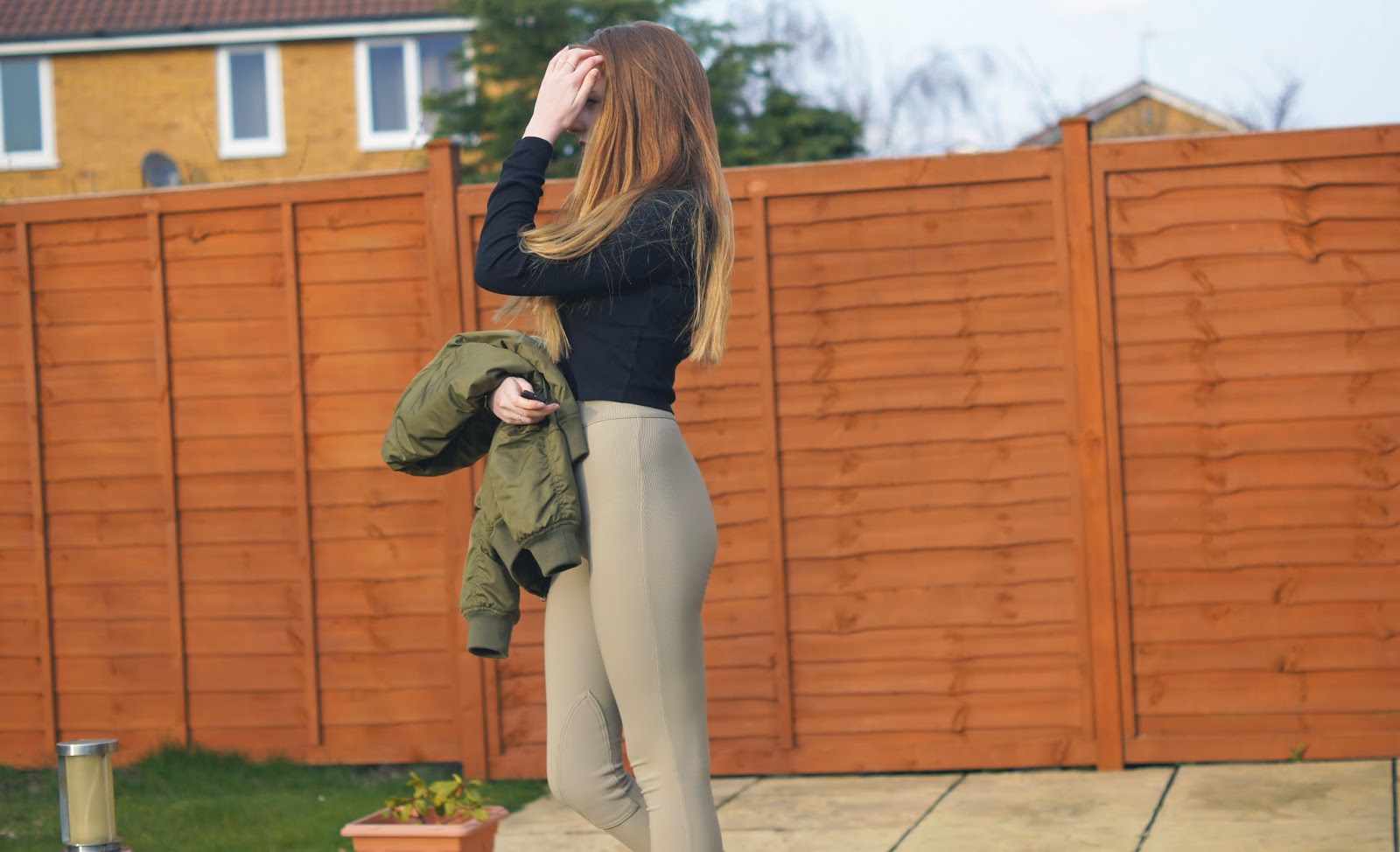 black turtle neck and camel trousers