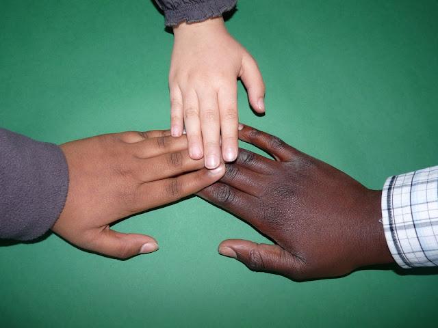 Tres manos de niños unidas