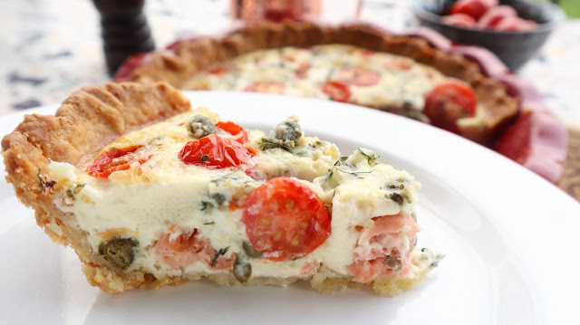 slice of the lower east side brunch tart with the full tart in the background.  side slice shows tomato, capers, smoked salmon and dill